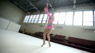 Rhythmic gymnastics: Girl training a gymnastics exercise with a clubs video