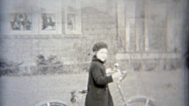 1937: Rich girl riding bike past mansions. video