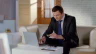 Rich man business suit inserting credit card number on laptop video