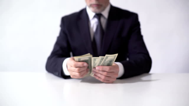 Rich man counting bundle of dollar banknotes, businessman estimating income video