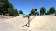 BMX rider grinds down rail, slow motion, speed ramp video