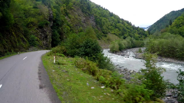 Riding on winding mountain road along fast-streamed river and steep cliffs video