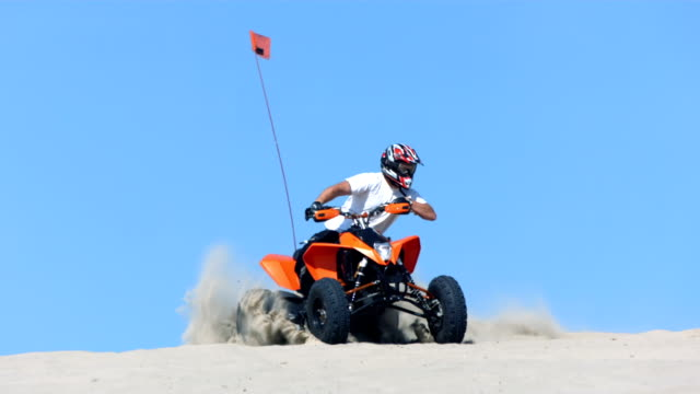 Riding quad in sand,  slow motion video