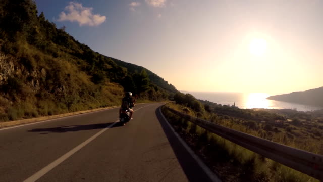 POV Riding scooter on a coast road at sunset video