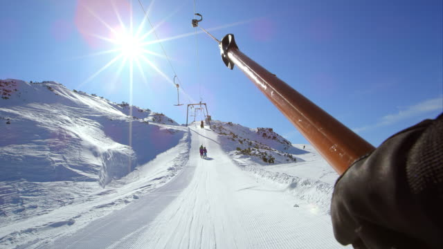 POV riding the surface ski lift up the sunny slope video