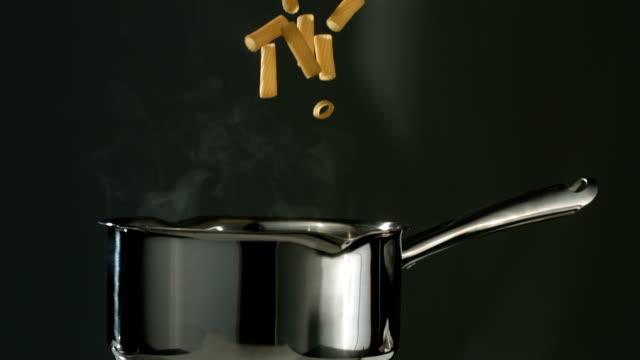 Rigatoni pasta falling into boiling water, slow motion video