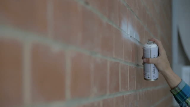 Right hand of man painting on brick wall with spray indoors video