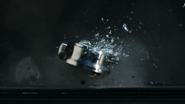 Ringing alarm clock is shot with gun, slow motion video