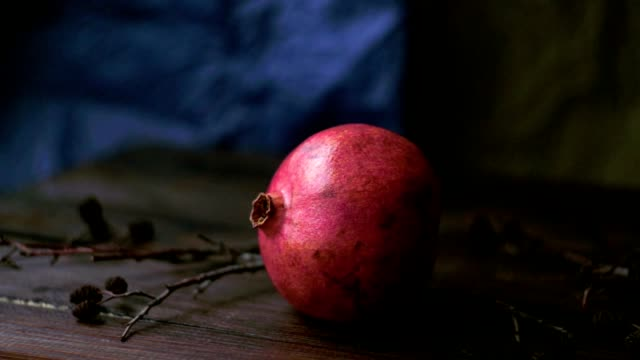Ripe pomegranate fruit. Red juice pomegranate on wooden background video