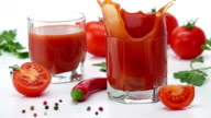 Ripe Tomato Falls into a Glass of Tomato Juice. video