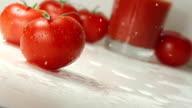 Ripe tomato falls on a table, splashing drops video