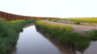A River and a Large Metal Fence Stretch into the Horizon video