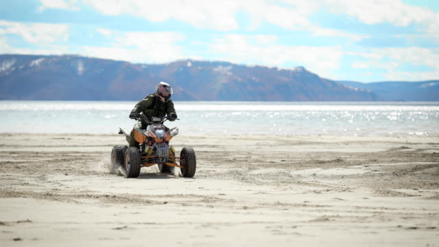 River bank. Sunny weather on the beach. A man is riding an ATV on fine sand. The racer on the ATV carries out roundabouts video