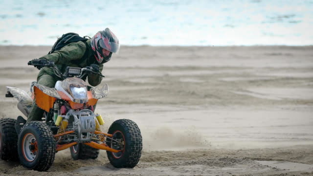 River bank. The racer works the movements on the quad bike. The man on the ATV studies driving at sand video