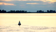 River landscape at sunset. Video is from the ship. A flock of birds flying over the water. The sky and clouds. The buoy in the fairway. The Volga River, Russia video