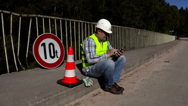 Road construction worker sitting and using tablet PC video