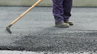 Road construction worker leveling asphalt using rake on the new road video