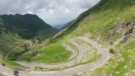 Road crossing mountain ridge at high altitude with cars driven between many spectacular curves and turns , aerial footage video