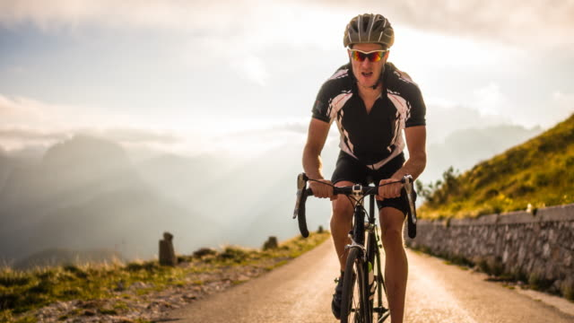 Road cycling on a mountain pass at sunset video