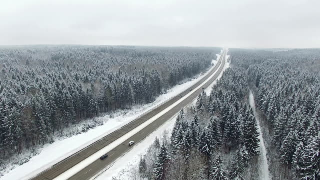 Road in the winter forest with driving cars. Aerial panoramic view. Vanishing point perspective. video