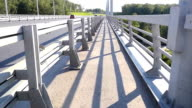 Road leading to a closed bridge in slowmotion. Metal supports of the bridge enclosure video