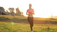 Road runner woman running in park in the morning motion track video