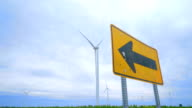 Road sign pointing to wing turbines field against clouds sky video