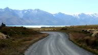 road through pasture near sea and distant snow mountains video