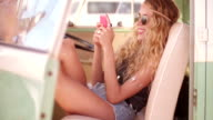 Road Trip Boho Girl Sitting in vintage Van with smartphone video