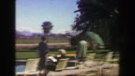 1947: Roadside hotel lounge area desert mountain range country club pool area. video