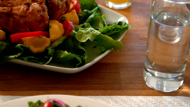 Roast chicken and salad on table video