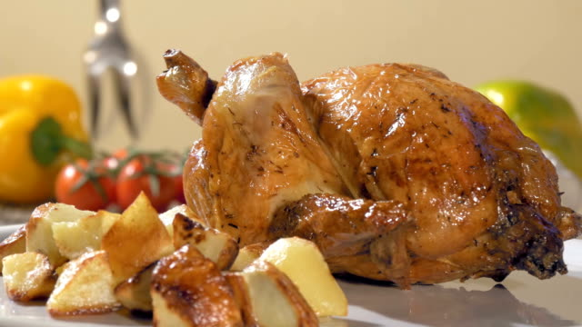 roast chicken with baked potatoes on stone plate rotating video