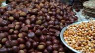 Roasted chestnut,  pine nut peeled and corn on street food stall. Autumn food of Asia video