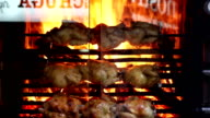 Roasted chickens on flamesover the glass window video
