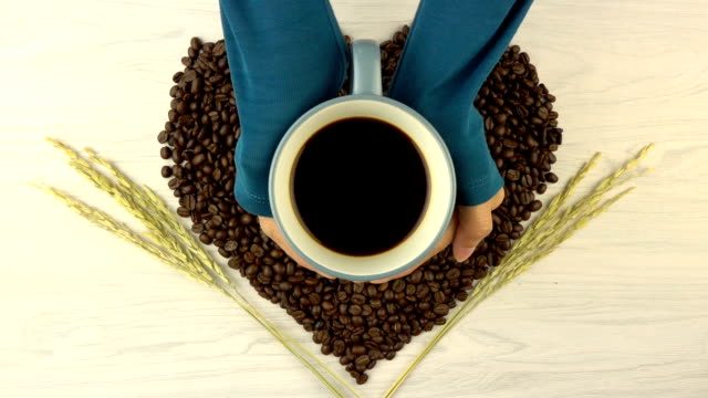 Roasted coffee beans in heart shape with coffee cup video