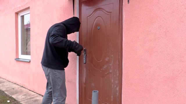 Robber with crowbar try to open door and watching to camera video
