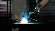 robotic welding arm welds metal parts video
