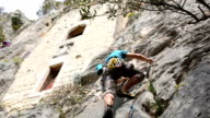 Rock climber ascends rock face below cliff dwellings video