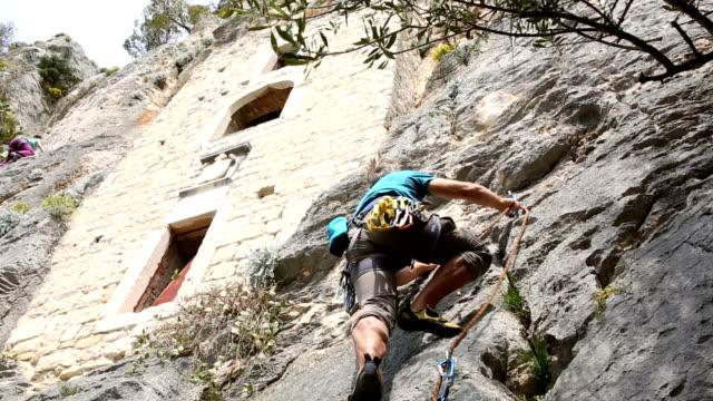 Rock climber ascends rock face below cliff dwellings video