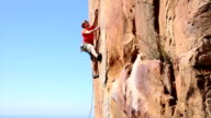 Rock climber ascends very steep cliff above meadow, sea video