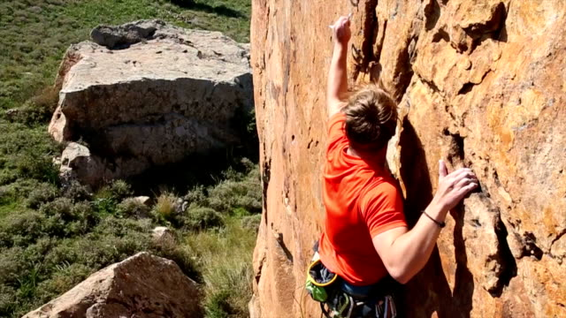 Rock climber ascends very steep cliff above meadow video