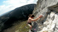 Rock climber high up on limestone cliff video