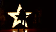 rock girl playing the electric guitar, shining star in the background. slow motion, silhouette video