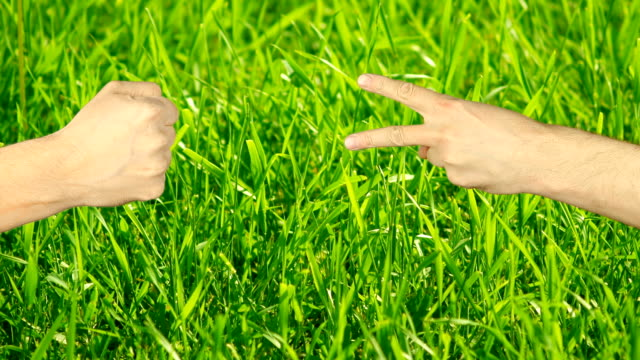 Rock paper scissors hand game. Two hands top aerial view. Green grass background. Hand gestures competition. Make choice. Random selection methods. Winner loser tournament. Play game gambling victory video