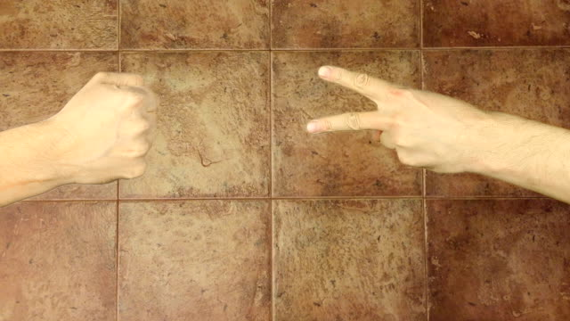 Rock paper scissors hand game. Two hands top aerial view. Tiled floor background. Hand gestures competition. Make choice. Random selection methods. Winner loser tournament. Play game gambling victory. video