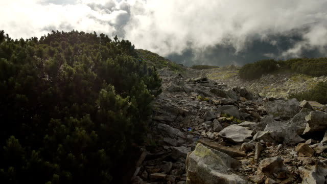 rocky high top of the mountain with fast moving clouds. sunset after the rain. smooth movement video