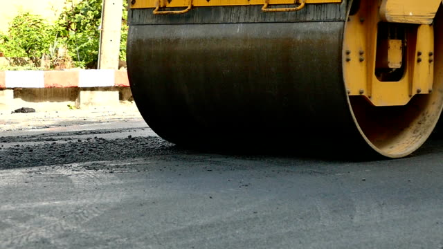 roller flattens asphalt,passing through the shot,close up. Paving and compacting new asphalt. video