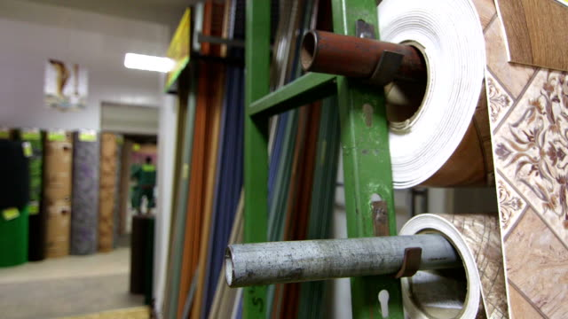 Rolls of linoleum and carpets in flooring warehouse video