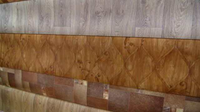 Rolls of linoleum in flooring warehouse pan shot video