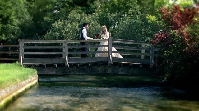 Romantic bride and groom kissing on a bridge video